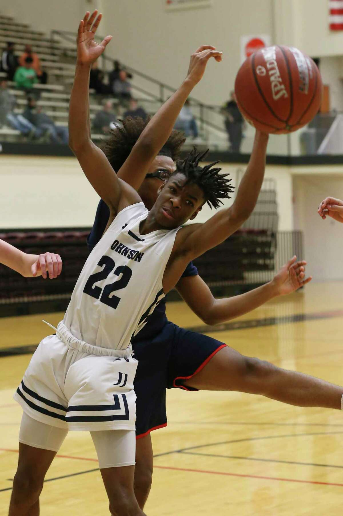 Johnson's Joseph Taylor goes for a rebound against Roosevelt's JaMarcus Hodge at Littleton Gym, Wednesday, Feb. 12, 2020.