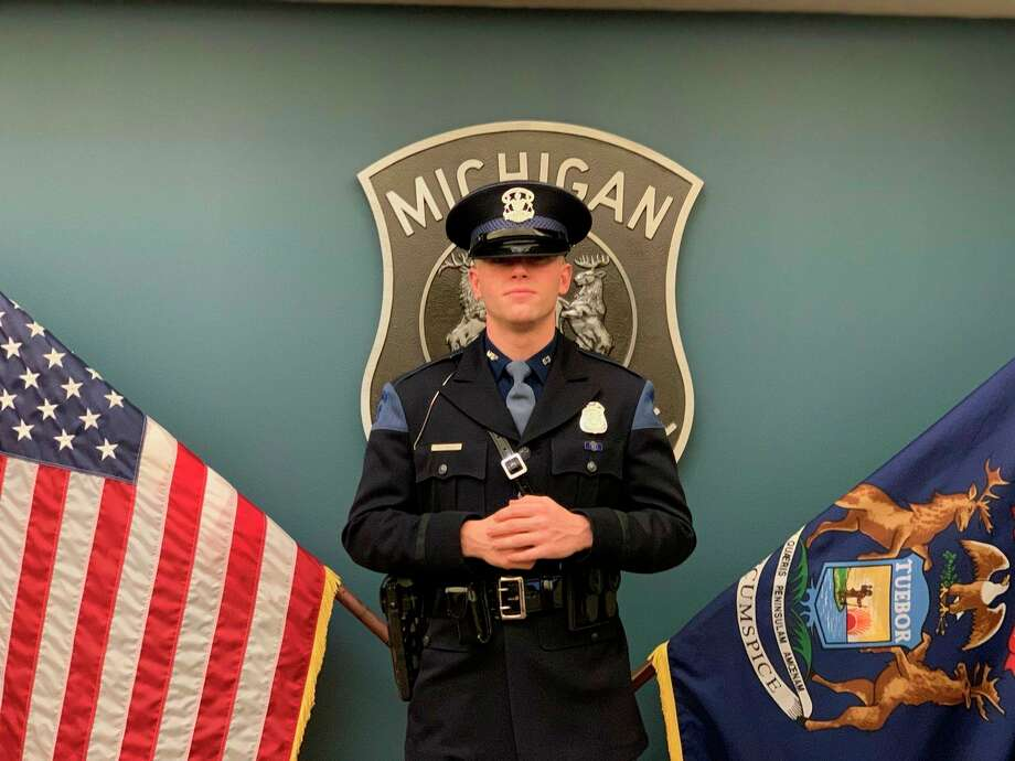Cody Bauer poses in front of the United States flag and Michigan's state flag after his graduation from the 136th Trooper Recruit School. A Midland High graduate, Bauer is now a Michigan State trooper serving in Mount Pleasant.