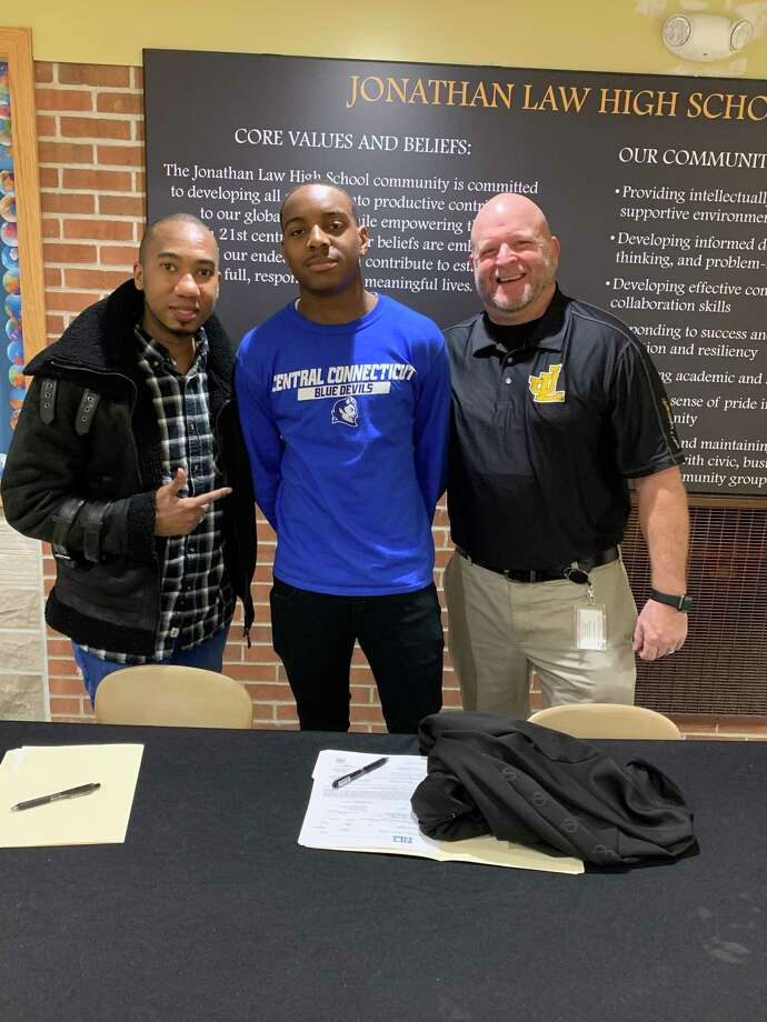Rayson Jacobs is joined by his uncle David McClure and Law track and field coach Joe Beler when he signed his letter of intent to play college football at Central Connecticut State University. Photo: Contributed Photo / Jonathan Law Athletics / Milford Mirror