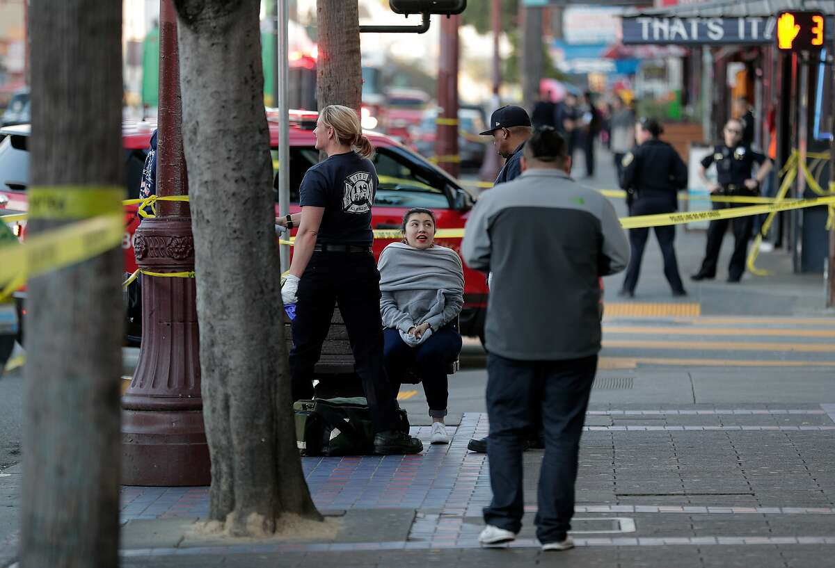 A woman who police identified as a witness is checked out by SFFD paramedics on Mission Street after a driver hit three pedestrians, left the scene and then returned to cooperate with police in San Francisco, Calif., on Wednesday, February 12, 2020.