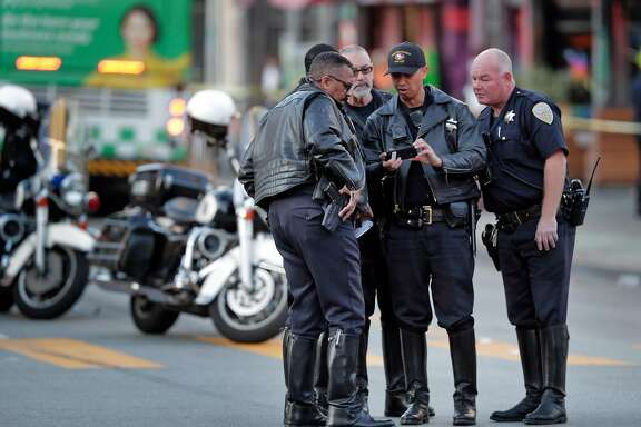 SFPD officers go over some pictures as they investigate the scene of a hit and run accident on Mission Street after a driver hit three pedestrians, left the scene and then returned to cooperate with police in San Francisco, Calif., on Wednesday, February 12, 2020.