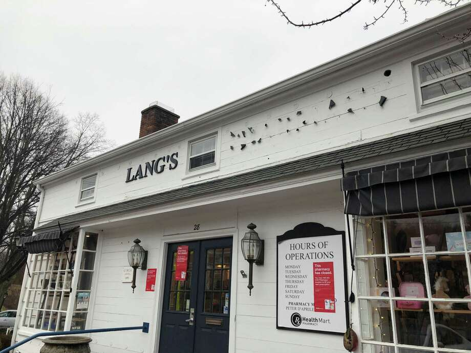 On Thursday, letters were being removed from the Lang's Pharmacy building in Wilton and red signs were put up advising prescription customers to contact CVS Pharmacy. Photo: Debra Hanson /Contributed Photo / Wilton Bulletin Contributed