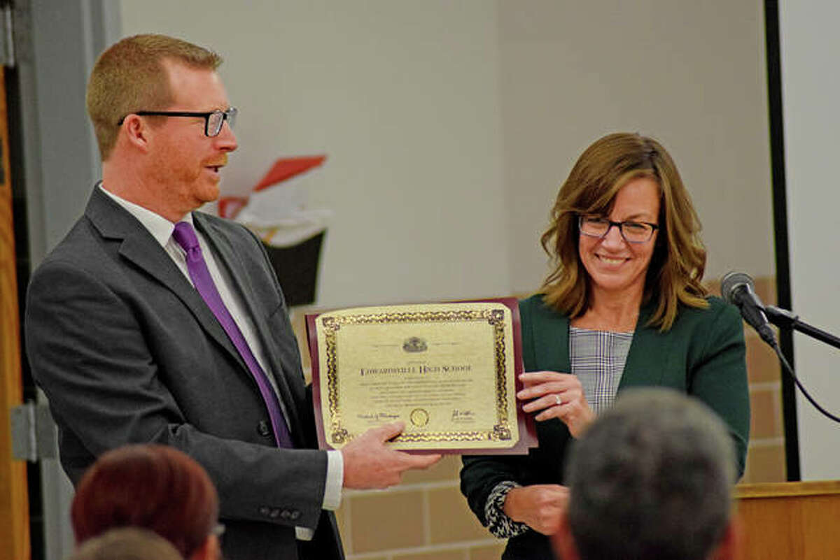 Paul Stuart, assistant principal at Edwardsville High School, accepts a certificate from State Representative Katie Stuart (D-Edwardsville) at District 7's School Board meeting Monday night.