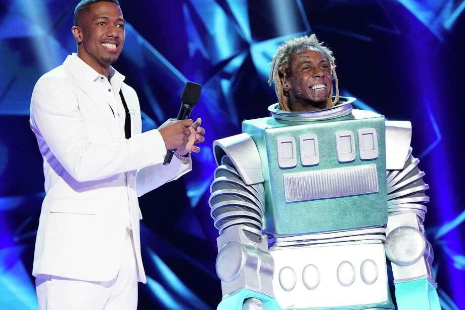 "Nick Cannon, left, with Lil Wayne in the third season premiere of ""The Masked Singer,"" which aired on Sunday after the Super Bowl. Photo: Associated Press / Fox"