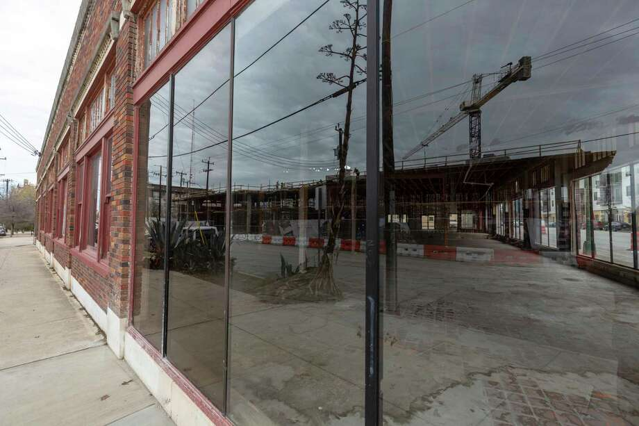 The still-under-construction Flats at River North apartments at the corner Jones Avenue and Broadway are are reflected Feb. 12, 2020 in the windows of a vacant building across the street. Photo: William Luther / ©2020 San Antonio Express-News