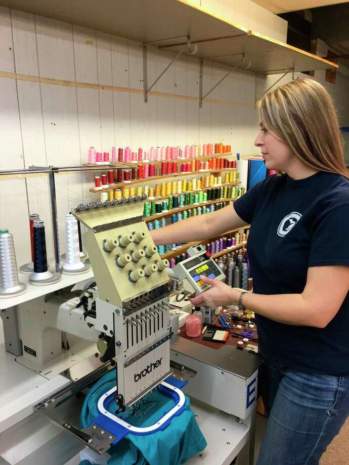 Great Lakes Custom Apparel Company LLC, owner Sarah Mowry works on a commercial embroidery machine. (Mary Drier/For the Tribune)