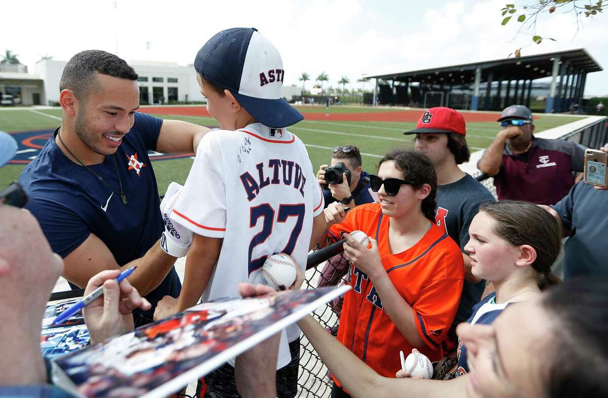 Houston Astros Carlos Correa signs autographs for Lucas Burris, 7, originally from Houston, during the first day of the Houston Astros pitchers and catchers spring training workout at the Fitteam Ballpark of The Palm Beaches, in West Palm Beach , Thursday, Feb. 13, 2020.