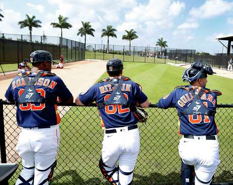 Houston Astros catchers Chuckie Robinson (83), Jamie Ritchie (82), and Lorenzo Quintana (81) wait their turns to catch pitchers during the first day of the Houston Astros pitchers and catchers spring training workout at the Fitteam Ballpark of The Palm Beaches, in West Palm Beach , Thursday, Feb. 13, 2020.