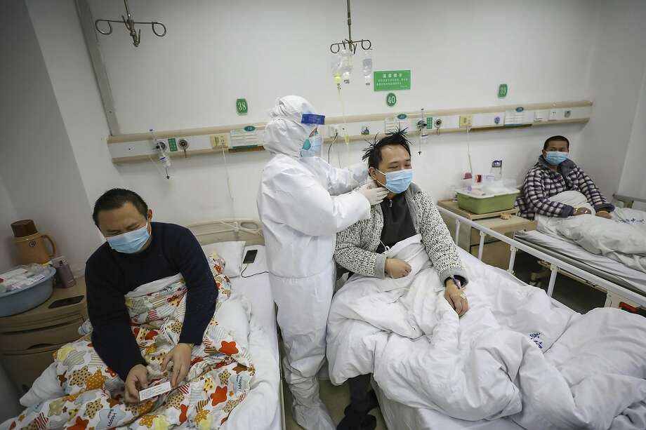 A doctor checks a patient in a hospital ward for those with COVID-19 virus in Wuhan city, Hubei province, the hardest-hit region in China for infections. Photo: Chinatopix