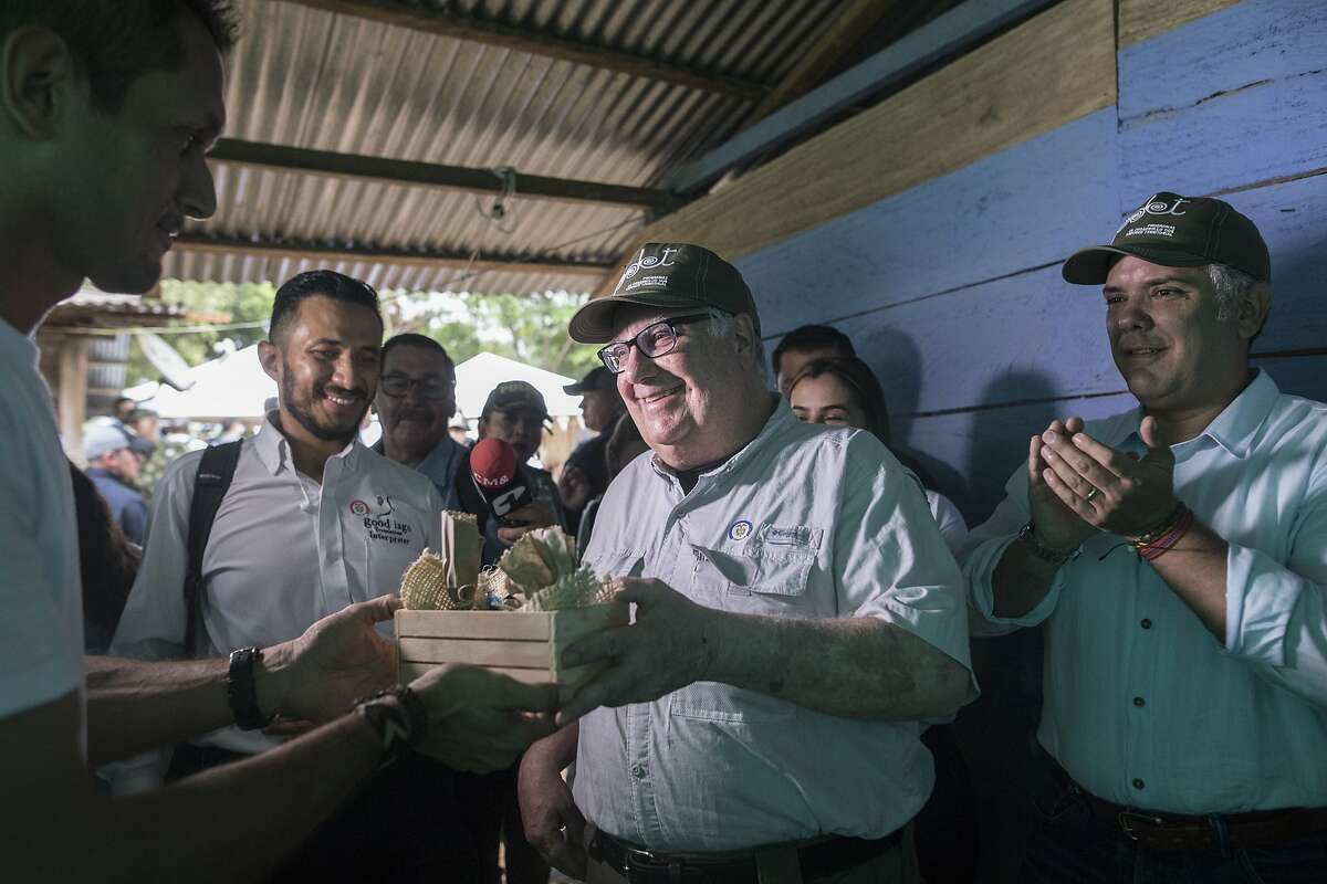 In this Jan. 29, 2020 photo, Howard Buffett receives presents during a visit, with Colombia's President Ivan Duque, right, to a cocoa farm in La Gabarra, Colombia. As a philanthropist, Buffett's priority now is helping Colombia and El Salvador, whose fight against drug trafficking has a direct impact on the U.S. (AP Photo/Ivan Valencia)