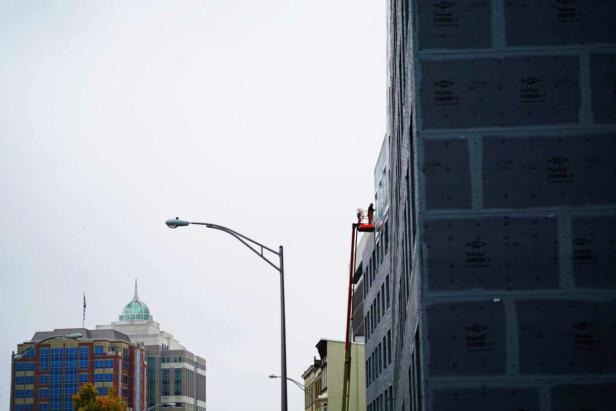 A worker is seen last October on a construction lift at the site of the 760 Broadway Apartments being built in Albany, N.Y. (Paul Buckowski/Times Union)
