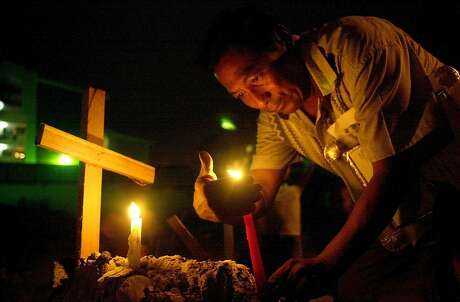 Ruben Dario Camargo lights a candle to mark the 11th anniversary of the U.S. military invasion in El Chorrillo, Panama City, Wednesday, Dec. 20, 2000. The invasion on Dec. 20, 1989, successfully removed dictator Manuel Noriega from power but at least 400 Panamanians died in the attack. Human rights groups give estimates that run into the thousands. About 20 American troops also died.