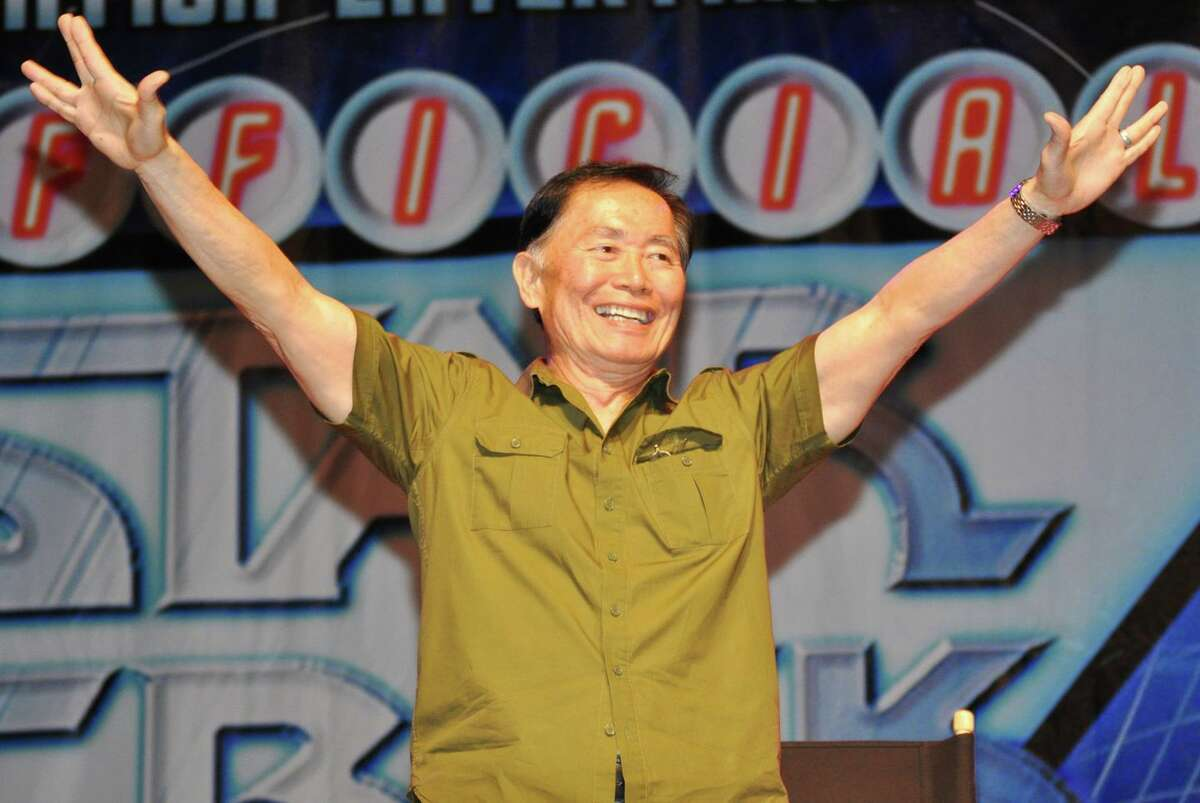 """George Takei makes the """"Star Trek"""" hand signal for """"live long and prosper"""" in greeting fans."""