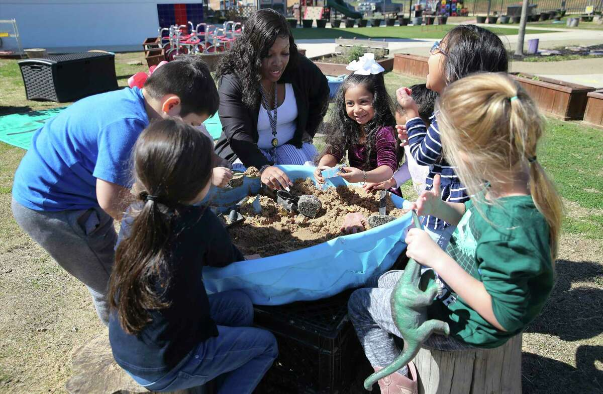Assistant teacher Monisha Fields gathers students around a sandbox at the Pre-K 4 SA South Education Center in February. A renewal of the program is on the November ballot.