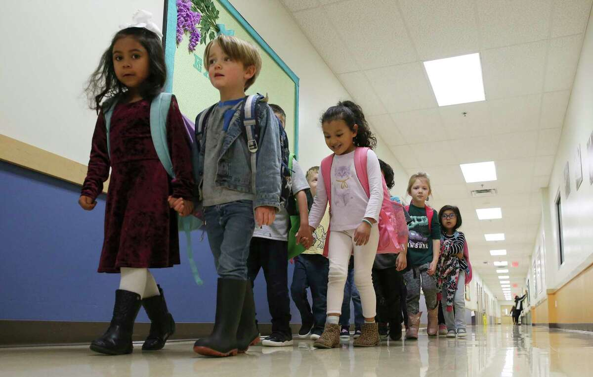 Pre-kindergarten students walk down a hallway singing and holding hands as they head outside for an activity at Pre-K 4 SA South Education Center.