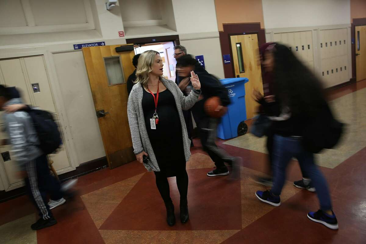 Aptos Middle School principal Nicole Trickett high fives a passing students while encouraging students to keep moving in the hallway to get to their next class at Aptos Middle School on Monday, January 27, 2020 in San Francisco, Calif.
