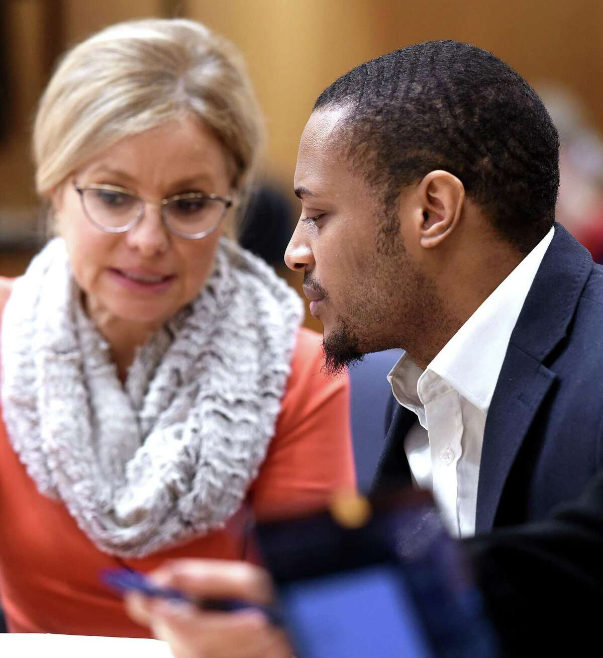 """Christopher Calhoun (right) speaks with attorney Tara Knight in Superior Court in New Haven on February 13, 2020 for the opening day of a trial for the 2011 killing of Isaiah """"King"""" Gantt."""