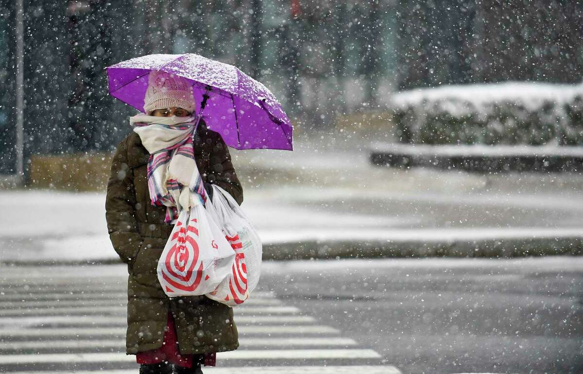 File photo of a woman bundled up from falling snow of a winter storm as she crosses Broad Street in downtown Stamford, Conn. on Dec. 9, 2017.