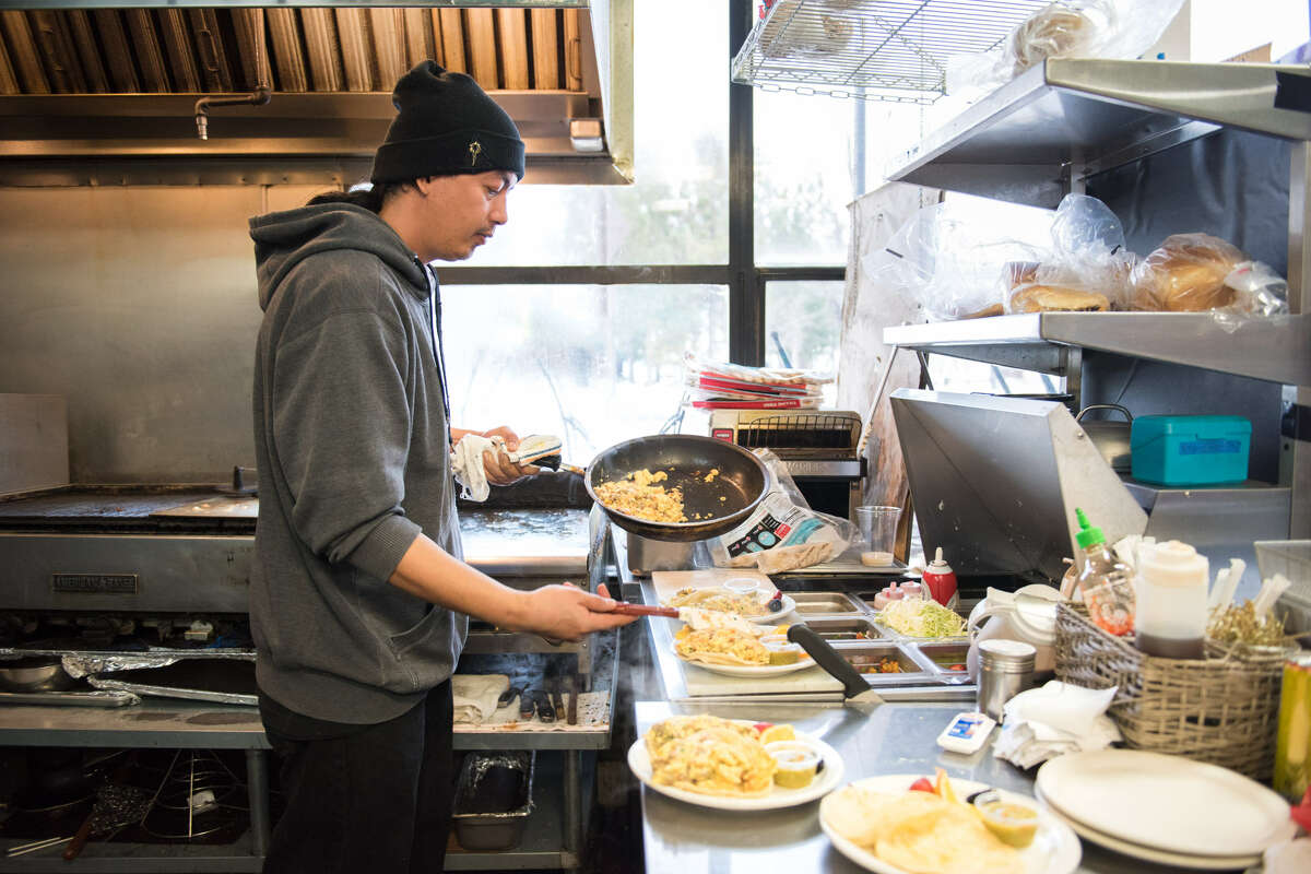 Billyjoe Aquino, a manager at Kings Cafe, works steadily in the kitchen preparing breakfast for a few regulars.