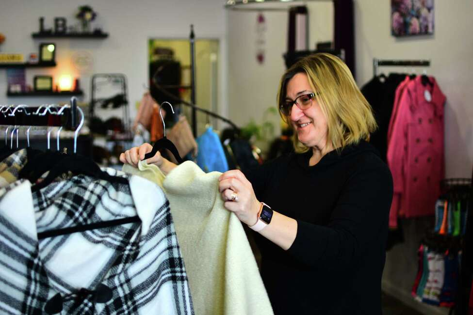 Darcy McCutcheon, owner of Livilu Boutique, a women's clothing store on Broadway in Rensselaer, examines merchandise on Wednesday, Feb. 12, 2020.