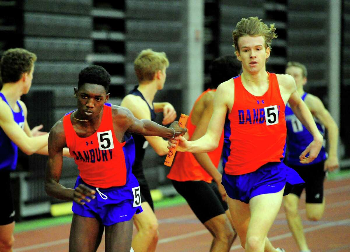 Danbury's Dylan Rosemark, right, hands the baton off to anchor Gabe Kwartemg in the 4x800 relay during the Class LL track championship in New Haven on Thursday.