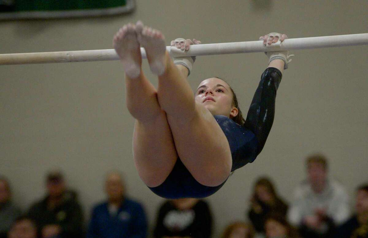 Newtown High School's Hannah Jojo competes in the uneven bars during the SWC gymnastics championships, Thursday night, February 13, 202, at New Milford High School, New Milford, Conn.