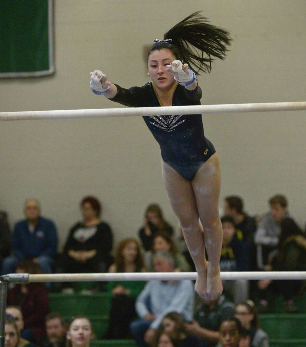 Newtown High School's Marisa Choi competes in the uneven bars during the SWC gymnastics championships, Thursday night, February 13, 202, at New Milford High School, New Milford, Conn.