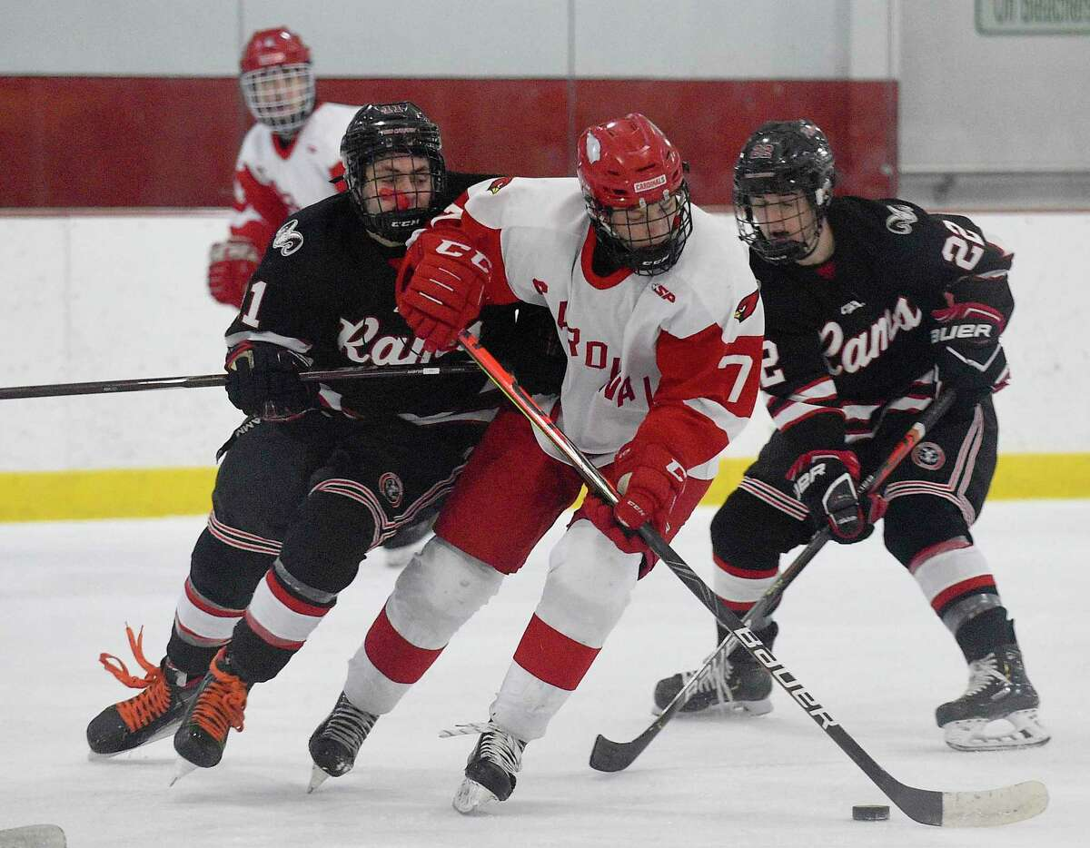 Greenwich's Wesley Zolin (7) drives on New Canaan's Bennet Ong (11) and Carter Spain during their game on Thursday at Dorothy Hamill Ice Rin in Greenwich.
