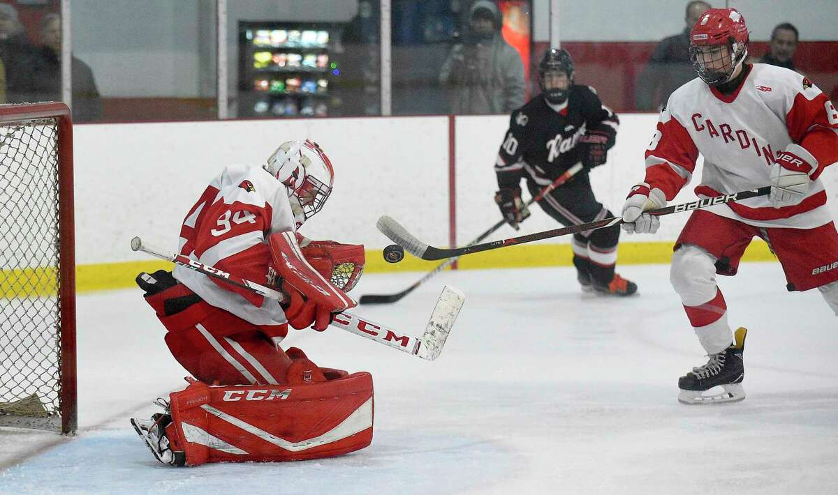 Greenwich goalie Charlie Zolin makes a save in front of the net against New Canaan in an FCIAC game at Dorothy Hamill Ice Rink in Greenwich in February.
