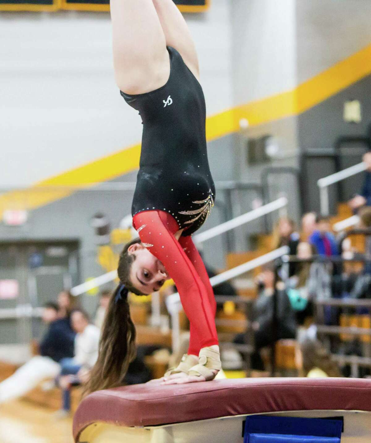 Branford's Brooke Kustra competes in the vault during the SCC gymnastics championship on Thursday.
