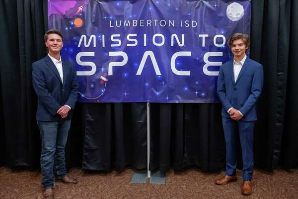 Austin Howard, left, and Lucas Mason stand by the Mission To Space banner in the school's performing arts center. The two students from Lumberton High School won a competition to send an experiment to the international space station this summer as part of the Student Spaceflight Experiments Program and the LISD held a night to honor them on February 13, 2020. Fran Ruchalski/The Enterprise