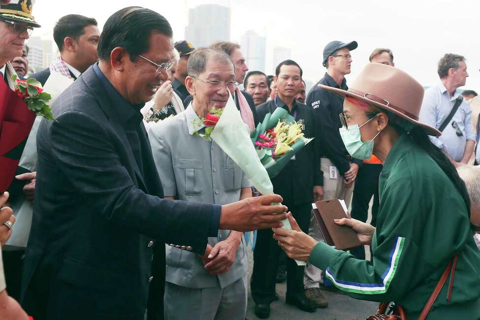 Cambodia's Prime Minister Hun Sen, left, gives a bouquet of flowers to a passenger who disembarked from the MS Westerdam, owned by Holland America Line, at the port of Sihanoukville, Cambodia, Friday, Feb. 14, 2020. Hundreds of cruise ship passengers long stranded at sea by virus fears cheered as they finally disembarked Friday and were welcomed to Cambodia. (AP Photo/Heng Sinith)