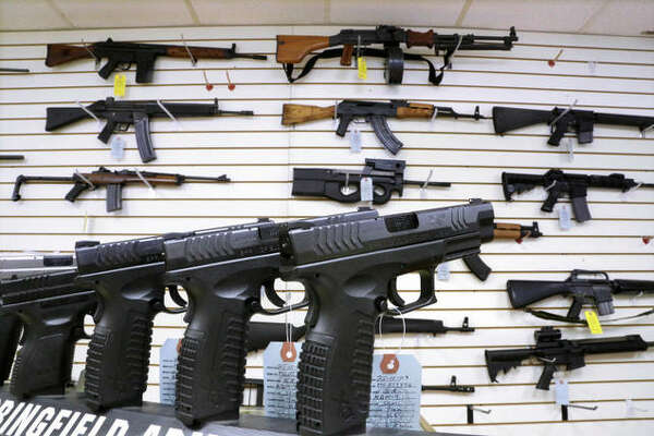 In this Jan. 16, 2013 photo, assault weapons and hand guns are seen for sale at Capitol City Arms Supply in Springfield, Ill. (AP Photo/Seth Perlman)