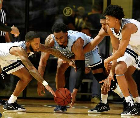 Rice guard Tommy McCarthy, left, and Old Dominion forward Aaron Carver, center, via for a loose ball during the first half of Thursday's game at Rice.