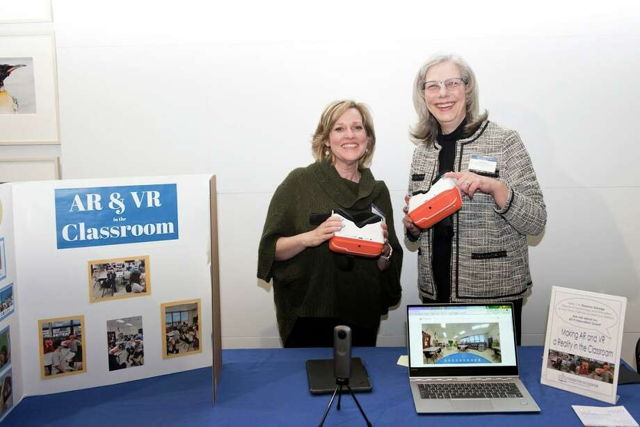 Deanna George, left, technology coordinator at Holy Trinity Catholic Academy and 2019 grant recipient, demonstrates Virtual Reality in the Classroom at the evening's festivities. George is with HTCA Head of School Lisa Lanni. Photo: AMY MORTENSEN / Connecticut Post