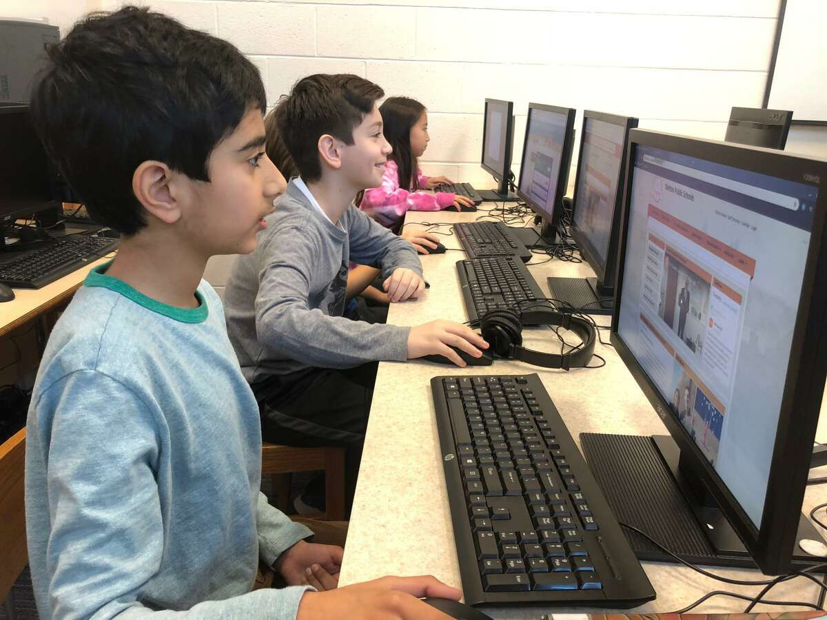 Booth Hill School fourth graders work on independent research projects under the guidance of school Library Media Specialist Andrea Clark.