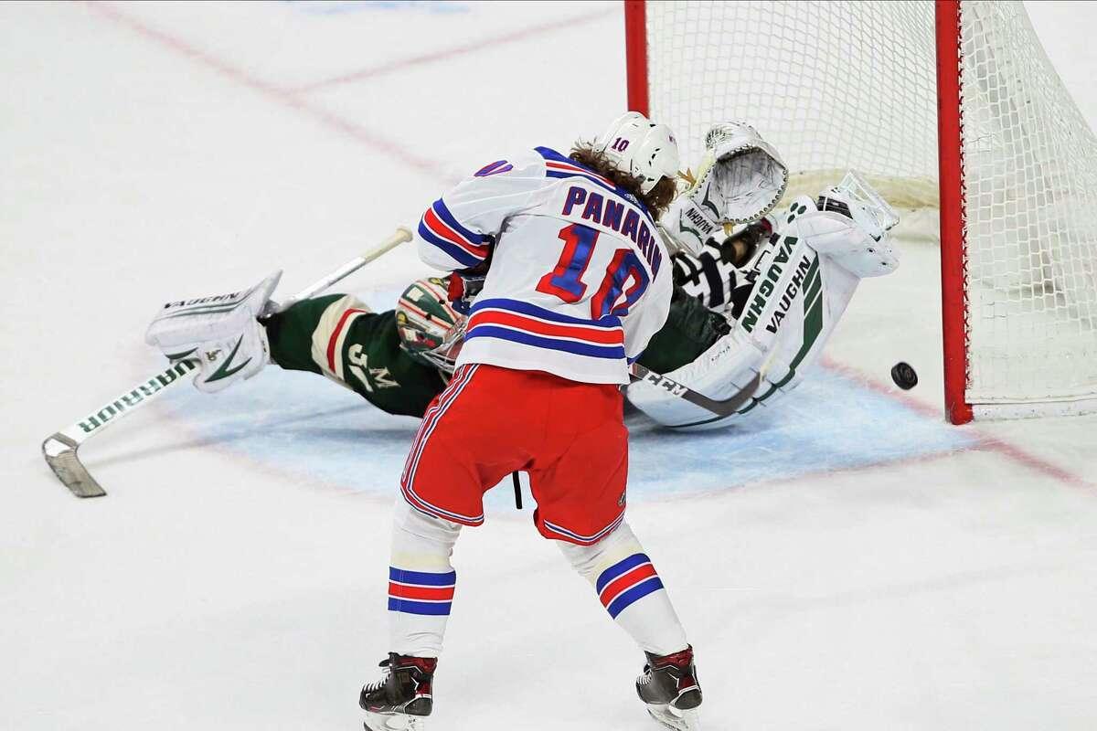 New York Rangers' Artemi Panarin, left, scores against Minnesota Wild's Alex Stalock during the shootout of an NHL hockey game Thursday, Feb. 13, 2020, in St. Paul, Minn. The Rangers won 4-3. (AP Photo/Jim Mone)