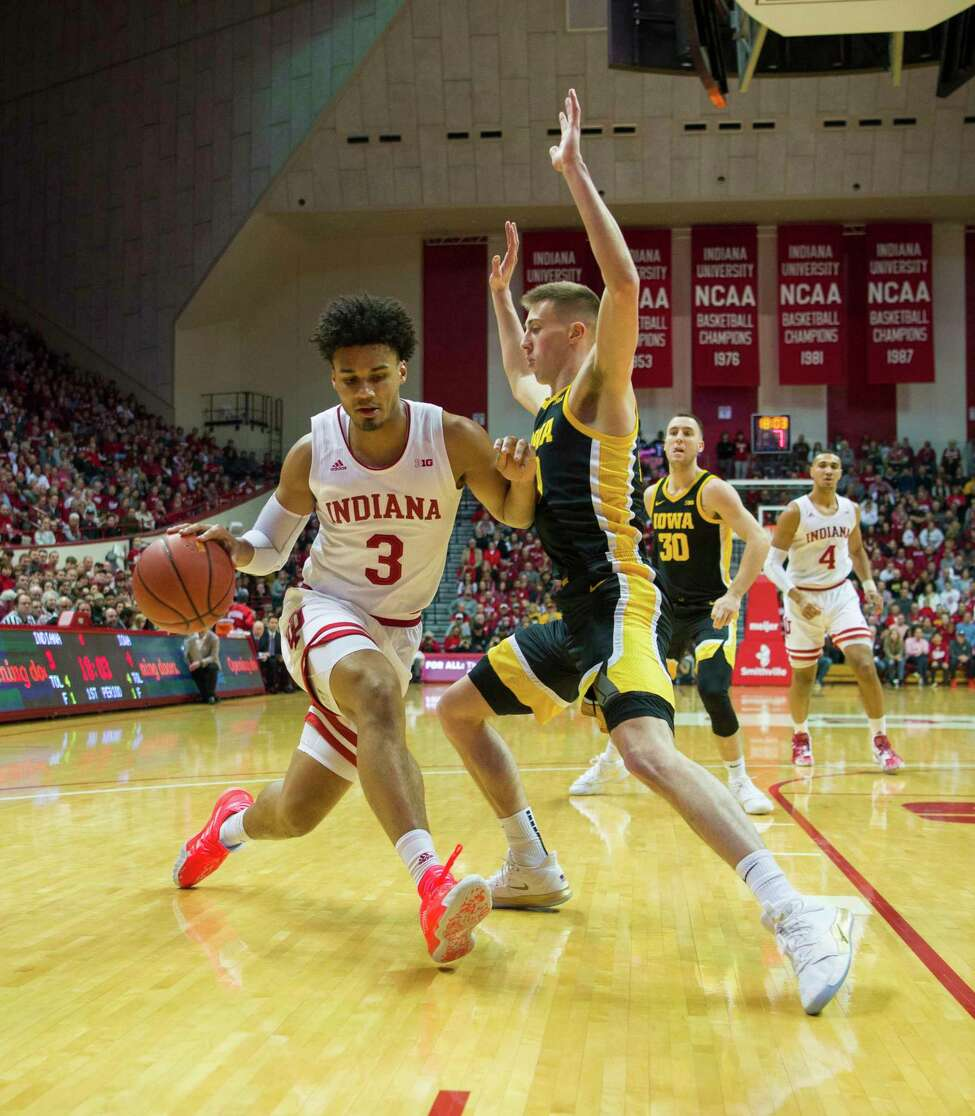 Indiana forward Justin Smith (3) is stopped along the baseline en route to the basket by Iowa guard Joe Wieskamp (10) during the first half of an NCAA college basketball game, Thursday, Feb. 13, 2020, in Bloomington, Ind. (AP Photo/Doug McSchooler)