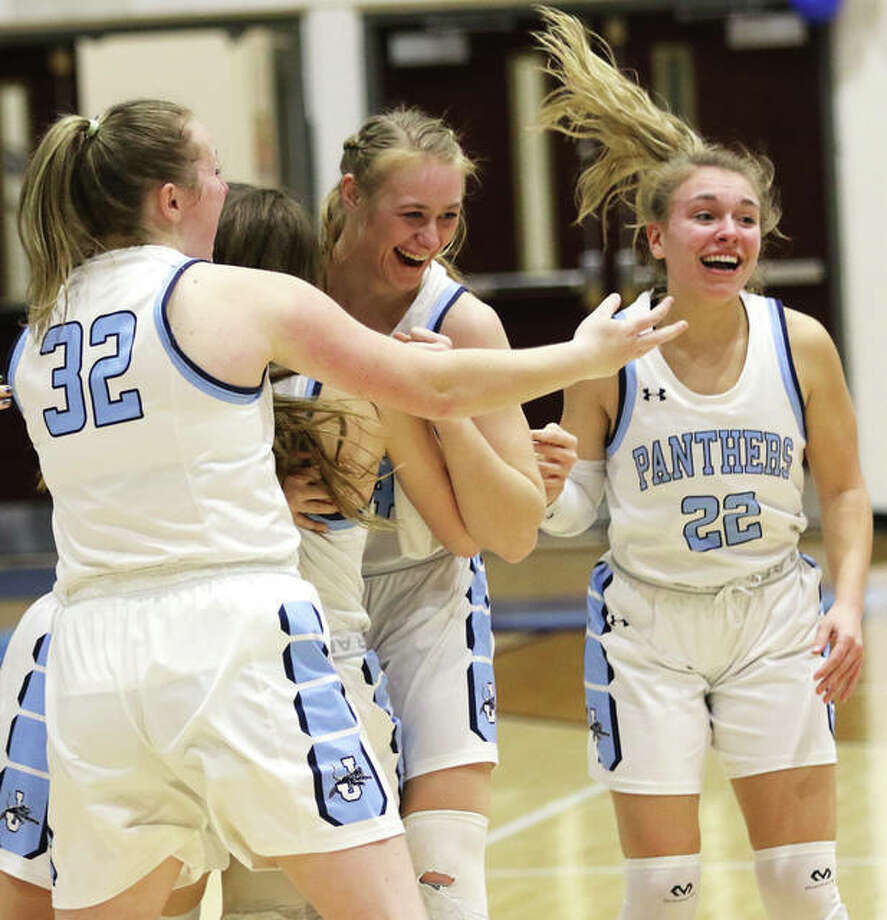 Jersey's Lauren Brown (middle) celebrates with teammates including Grace Myers (32) and Clare Breden (22) after Brown's layup with one second left gave the Panthers a 64-63 victory over Civic Memorial on Thursday night at Havens Gym in Jerseyville. The loss ended CM's 33-game MVC winning streak. Photo: Greg Shashack | The Telegraph