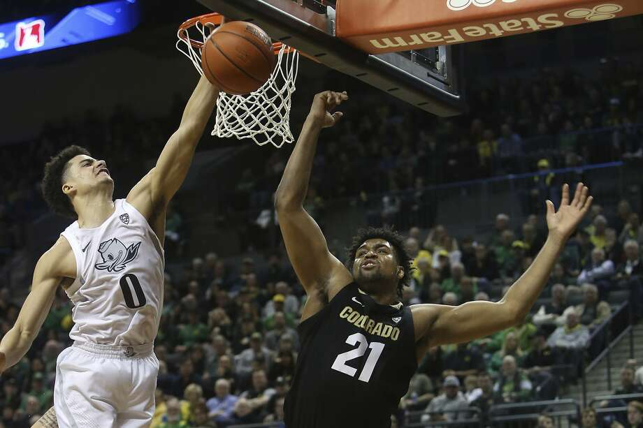 Oregon's Will Richardson and Colorado's Evan Battey (21) battle for a rebound in the Ducks' win in Eugene, Ore. Photo: Chris Pietsch / Associated Press