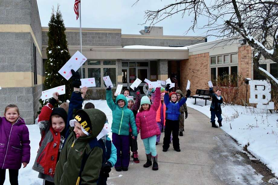 Bear Lake first graders proudly hold up their Valentine's letters to their parents complete with a heart on them that they mailed out at the post office. (Courtesy photo)