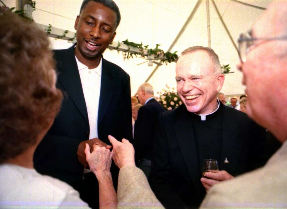 """Rev. Kevin E. Mackin - 1996-2007 """"If your work and life makes the lives of others better, then you indeed can look upon that and see that it is very good,"""" Mackin told new Siena graduates in 2003. In this photo, guests chat with Siena College head basketball coach Louis Orr, left, and the Siena College President Rev. Mackin at the Teresian House Tenth Annual Fundraiser Gala at the Reading Room in Saratoga Springs in 2000."""