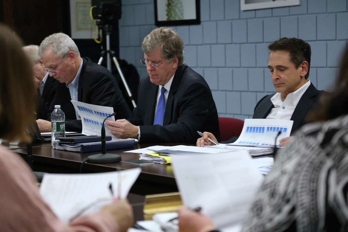 Before the pandemic changed everything, Board of Finance members Jeff Rutishauser, Michael Kaelin and Stewart Koenigsberg look over Board of Education documents on Feb. 6.