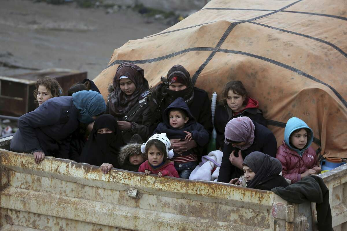FILE - In this January 30, 2020 file photo, Syrians sit in the back of a truck fleeing the advance of government forces, as they head towards the Turkish border, in Idlib province, Syria. Hundreds of thousands of Syrians have fled recent government bombardment of the last rebel bastion, the northwestern Idlib province, seeking shelter from harsh winter weather in muddy tents and half-constructed buildings. As government forces advance, areas deemed safe are rapidly shrinking. (AP Photo/Ghaith al-Sayed, File)