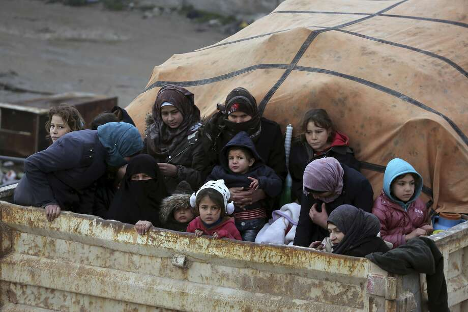 Syrians sit in a truck fleeing the advance of government forces in Idlib province Jan. 30 as they head toward the Turkish border. Hundreds of thousands of have fled the advance. Photo: Ghaith Al-Sayed / Associated Press