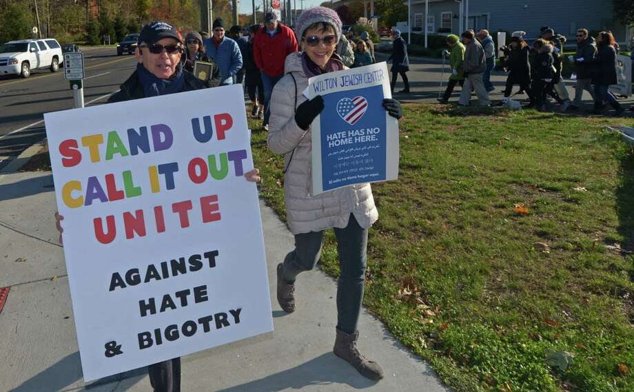 A march against hate and bigotry organized by Scott Milnor, left, and Susan Cutler, right, moves through Wilton Center from the Wilton Train Station in 2017. Photo: Erik Trautmann / Hearst Connecticut Media / Norwalk Hour