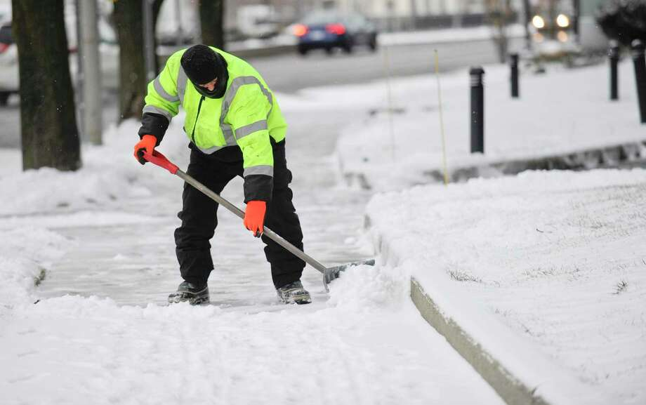 A worker clears the sidewalks in front of 1055 Washington Blvd. following a winter storm on Jan. 18 in Stamford that left travelers with slippery conditions and 1-2 inches of snow. It was one of the few snowstorms of this winter. Photo: Matthew Brown / Hearst Connecticut Media / Stamford Advocate