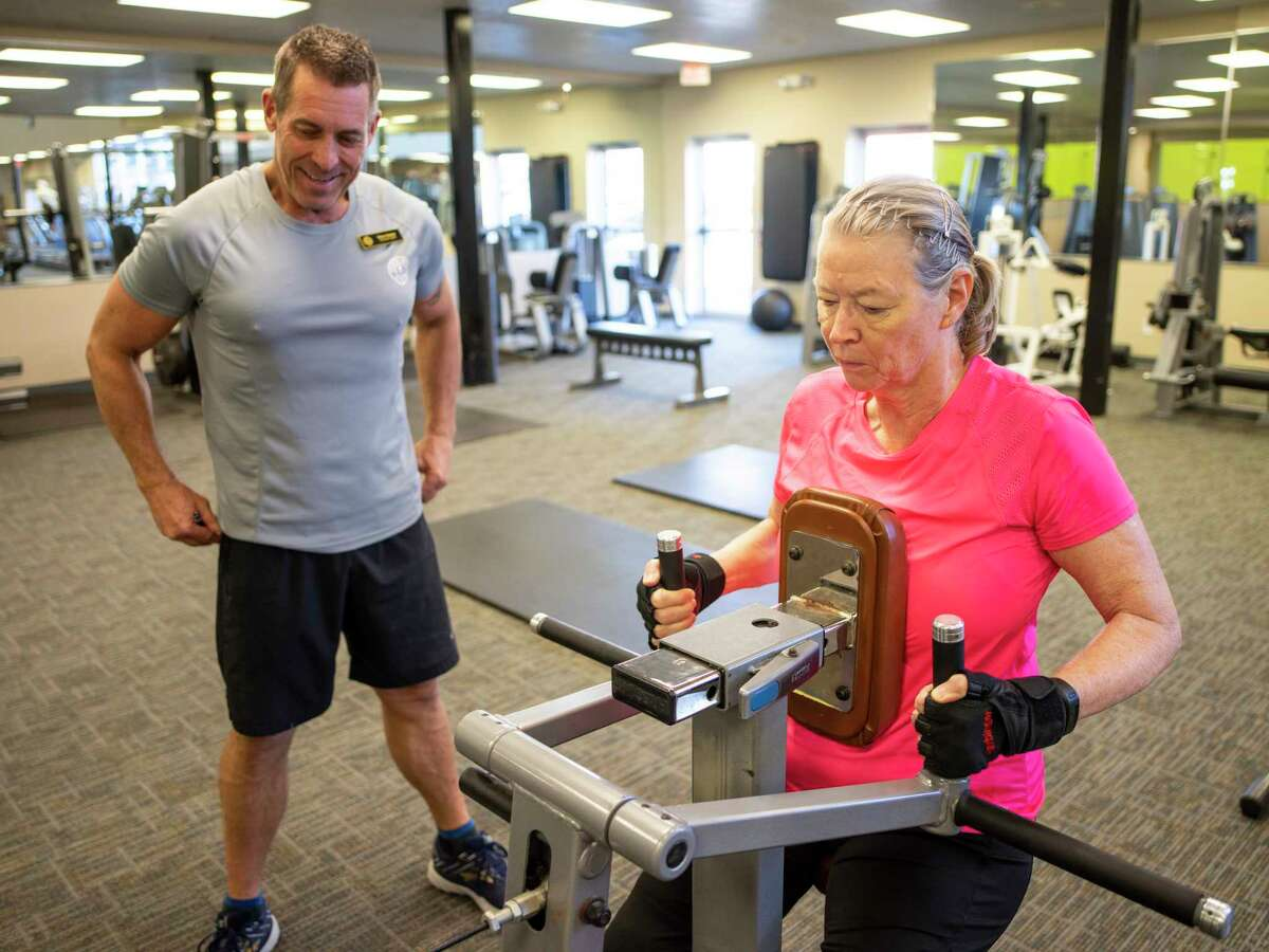 Rose Ramirez, right, 65, exercises using a back machine at Gold?•s Gym as her personal trainer Steve Suesz, left, records her workout in San Antonio, Texas, on Monday, December 30, 2019. Ramirez is a retired Air Force Colonel who served in the military for 38 years. After being diagnosed with Ovarian Cancer in August 2017, Ramirez underwent chemotherapy and has been cancer-free since September 2018. She has since started a workout regime at Gold?•s Gym with a personal trainer, Steve Suesz, who has her performing exercises to improve her balance and strength. ?'My goal is the be strong and able to move,?