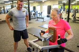 Rose Ramirez, right, 65, exercises using a back machine at GoldÕs Gym as her personal trainer Steve Suesz, left, records her workout in San Antonio, Texas, on Monday, December 30, 2019. Ramirez is a retired Air Force Colonel who served in the military for 38 years. After being diagnosed with Ovarian Cancer in August 2017, Ramirez underwent chemotherapy and has been cancer-free since September 2018. She has since started a workout regime at GoldÕs Gym with a personal trainer, Steve Suesz, who has her performing exercises to improve her balance and strength. ÒMy goal is the be strong and able to move,Ó Ramirez said. Personal trainer Suesz, who has a certification in senior fitness, says that as people get older, their muscle strength atrophies, and it becomes easier for their bones to break. Suesz has structured RamirezÕs workout regimen to be proactive when it comes to performing everyday tasks and to help her maintain a healthy balance of strength and flexibility.