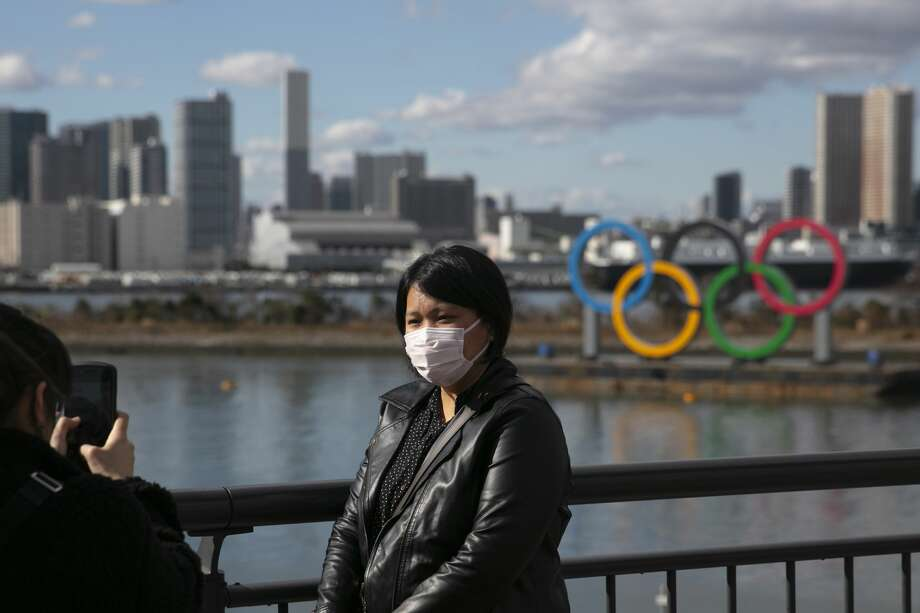 FILE - In this Jan. 29, 2020, file photo, a tourist wearing a mask poses for a photo with the Olympic rings in the background, at Tokyo's Odaiba district. Tokyo Olympic organizers repeated their message at the start of two days of meetings with the IOC: this summer's games will not be cancelled or postponed by the coronavirus spreading neighboring China. (AP Photo/Jae C. Hong, File) Photo: Jae C. Hong/Associated Press